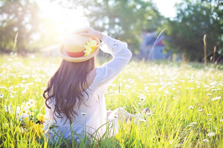 Eine Frau auf blühender Wiese mit Sonnenstrahlen