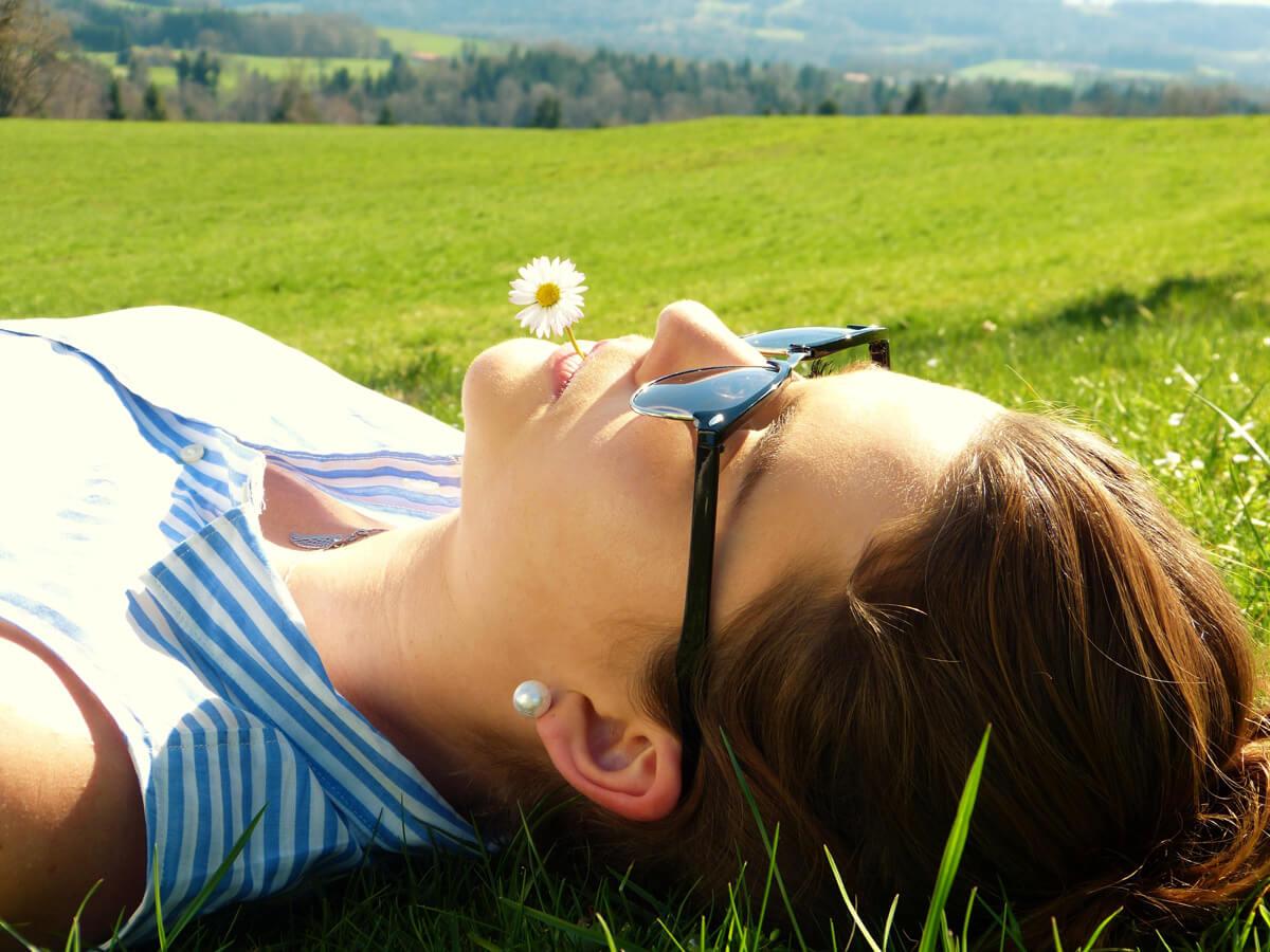 Digital Detoxing - junge Frau auf Wiese