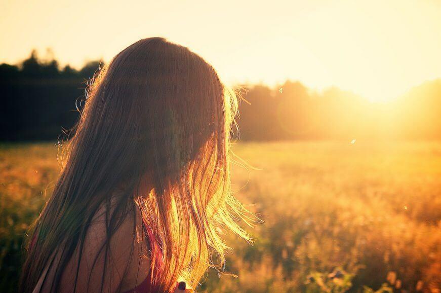 Rückzug und Erholung - Ein Frau sitzt in der Abendsonne auf einer Wiese und wird von goldenem Sonnenlicht umstrahlt